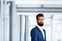 Junges hübsches Geschäftsmann-Standing At Company-` s Innen stockfotografie
