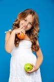 Junges hübsches Mädchen, das Apfel und Orange über blauem Hintergrund hält Lizenzfreie Stockfotografie