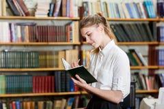 Junges hübsches Mädchen, das an der Kamera in der Bibliothek aufwirft getrennte alte Bücher Lizenzfreies Stockfoto