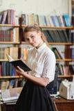 Junges hübsches Mädchen, das an der Kamera in der Bibliothek aufwirft getrennte alte Bücher Stockfotos