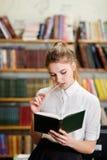 Junges hübsches Mädchen, das an der Kamera in der Bibliothek aufwirft getrennte alte Bücher Stockfoto