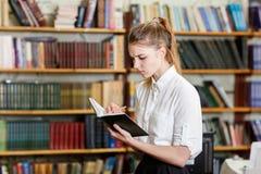 Junges hübsches Mädchen, das an der Kamera in der Bibliothek aufwirft getrennte alte Bücher Stockbild
