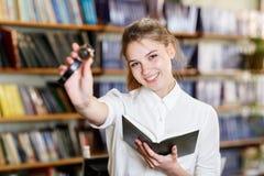 Junges hübsches Mädchen, das an der Kamera in der Bibliothek aufwirft getrennte alte Bücher Stockfotografie