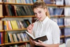 Junges hübsches Mädchen, das an der Kamera in der Bibliothek aufwirft getrennte alte Bücher Lizenzfreie Stockfotografie