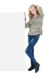 Junges hübsches Mädchen, das ein leeres Schild getrennt auf Weiß anhält Lizenzfreie Stockfotografie