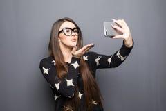 Junges hübsches Mädchen, das ein selfie macht und einen Kuss auf grauen Hintergrund sendet Lizenzfreie Stockbilder