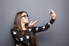 Junges hübsches Mädchen, das ein selfie macht und einen Kuss auf grauen Hintergrund sendet Stockfotografie
