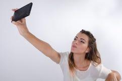 Junges hübsches Mädchen, das ein selfie macht und einen Kuss sendet Stockfotografie