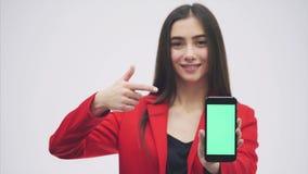 Junges hübsches hübsches Mädchen, das eine rote Jacke trägt Aufenthalte auf einem grauen Hintergrund Während dieser Zeit hält ein stock video