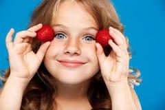 Junges hübsches Mädchen, das Erdbeere über blauem Hintergrund hält stockfoto