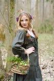 Junges hübsches Mädchen, das im Wald mit Korb von Blumen aufwirft stockfoto