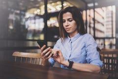 Junges hübsches Mädchen, das an Laptop arbeitet und mobilen Smartphone an ihrem Arbeitsplatz in der modernen Büromitte verwendet  lizenzfreies stockfoto