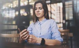 Junges hübsches Mädchen, das an Laptop arbeitet und mobilen Smartphone an ihrem Arbeitsplatz in der modernen Büromitte verwendet  stockfotografie