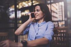 Junges hübsches Mädchen, das an Laptop arbeitet und mobilen Smartphone an ihrem Arbeitsplatz in der modernen Büromitte verwendet  stockbild