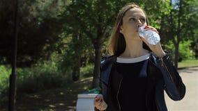 Junges hübsches Mädchen, das Mineralwasser trinkt stock footage
