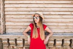 Junges hübsches Mädchen, das nahe hölzerner Wand im roten Kleid, im Hut und in der Sonnenbrille steht Sommerberufung Lizenzfreies Stockfoto