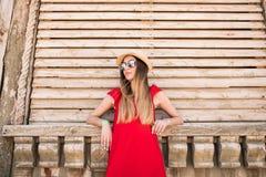 Junges hübsches Mädchen, das nahe hölzerner Wand im roten Kleid, im Hut und in der Sonnenbrille steht Sommerberufung Lizenzfreie Stockfotos
