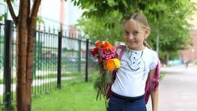 Junges hübsches Mädchen, das nahe Schule mit sonnigem Tag des Rucksacks und der Blumen steht Zurück zu Schule Schulmädchen gehen  Lizenzfreies Stockbild