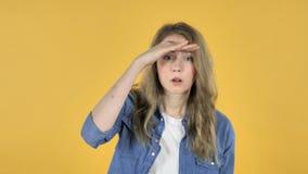 Junges hübsches Mädchen, das neue Möglichkeit, gelben Hintergrund sucht stock video