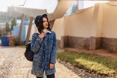 Junges hübsches Mädchen in einem Denimmantel geht in die Herbststadt stockbilder