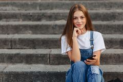 Junges hübsches Mädchen mit dem Aktenkoffer, der auf Treppe sitzt und s schreibt stockfotografie