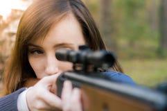 Junges hübsches Mädchen mit Gewehr Stockfoto