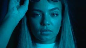 Junges hübsches Mädchen nahe glühenden Neonlichtern der Stadt nachts Hippie-Jugendlicher in den Gläsern und in den schönen Linsen stock video footage