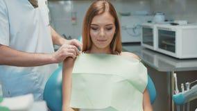 Junges hübsches Mädchen und Zahnarzt, die für zahnmedizinische Behandlung sich vorbereitet 4K stock video
