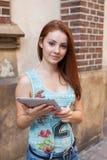 Junges hübsches Mädchen, welches das on-line-Einkaufen unter Verwendung der Tablette tut Städtisches BAC Stockfotografie