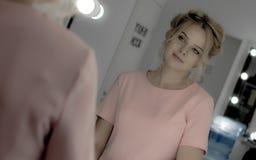 Junges hübsches Modell mit Berufsmake-upblick auf Spiegel im Make-upraum Stockfotografie