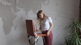 Junges h?bsches blondes M?dchen mit B?rsten- und Palettenstellung nahe Gestellzeichnungsbild Kunst, Kreativit?t stock video footage