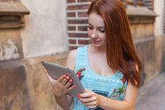 Junges hübsches Mädchen, welches das on-line-Einkaufen unter Verwendung der Tablette tut Städtisches BAC Lizenzfreies Stockfoto