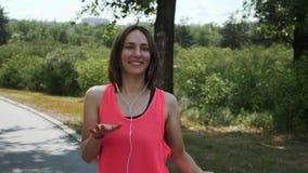 Junges heißes attraktives Mädchentanzen im Park Sportives Mädchen im rosa Hemdlächeln Brunette Mädchen in den Kopfhörern mit Smar stock video