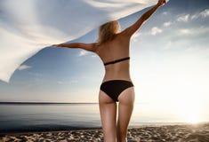 Junges herrliches blondes am Sonnenuntergang auf dem Strand Stockfoto