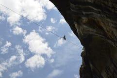 Junges highliner, das hoch auf ein Drahtseil im Himmel geht Lizenzfreie Stockbilder