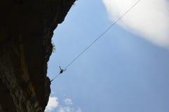 Junges highliner, das hoch auf ein Drahtseil im Himmel geht Stockfotografie