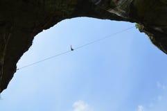 Junges highliner, das hoch auf ein Drahtseil im Himmel geht lizenzfreies stockbild