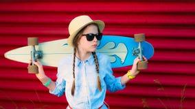 Junges Hippie-Mädchen mit Borten in der Sonnenbrille und im Strohhut Stockfotos