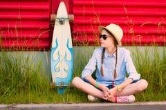 Junges Hippie-Mädchen mit Borten in der Sonnenbrille und im Strohhut Stockfoto