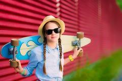 Junges Hippie-Mädchen mit Borten in der Sonnenbrille und im Strohhut Stockbild