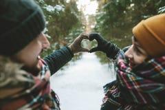 Junges Hippie-Paarhändchenhalten im Liebessymbol Stockfoto