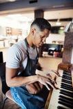 Junges hispanisches haidresser und Herrenfriseur, die im Friseursalon, Klavier spielend sitzt lizenzfreie stockbilder