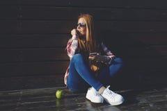 Junges Hochschulstudentinholding-Zelltelefon bei der Entspannung nach Vorträgen stockfoto