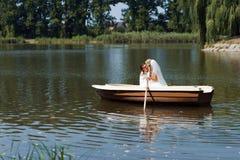 Junges Hochzeitspaarsegeln auf dem Boot lizenzfreie stockbilder