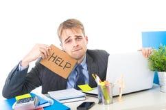 Junges hoffnungsloses Geschäftsmannholding-Hilfszeichen, das gesorgte leidende Belastung Computertisch betrachtet Lizenzfreie Stockfotografie