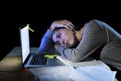 Junges hoffnungsloses Hochschulstudentmädchen im Druck für Prüfung spät studierend mit Büchern und Computerlaptop nachts Stockbild