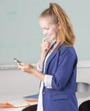 Junges Holding-Mobiltelefon der erwachsenen Frau im Büro Stockbilder