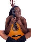 Junges impliziertes Akt der schwarzen Frau hinter Gitarre Lizenzfreies Stockfoto