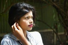 Junges indisches Mädchen mit dem kurzen Haar mit ihrer Hand nahe dem Ohr, das weg schaut und für Kamera in einem Sonnenlicht, P lizenzfreie stockfotografie