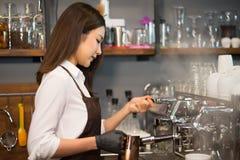 Junges Inhaber barista, das dämpfende Milch mit Kaffeemaschine zubereitet Lizenzfreies Stockbild